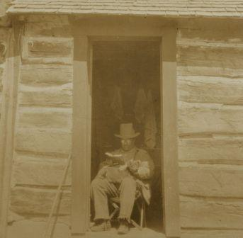 Theodore Roosevelt reading in his West Divide cabin on Colorado hunting trip, 1905.